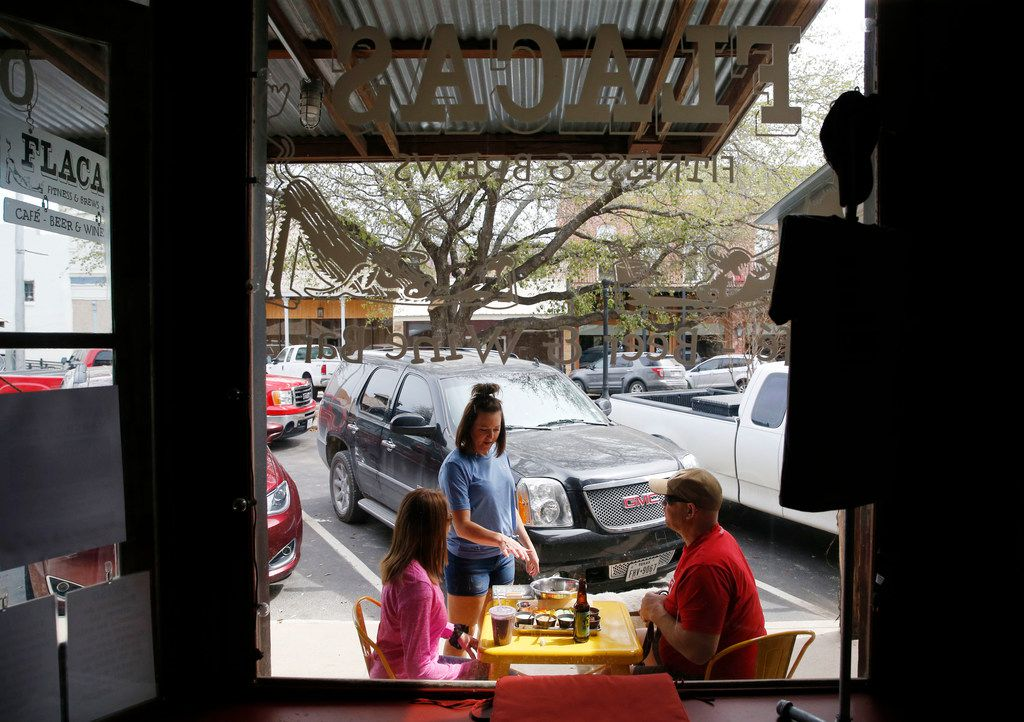 Manager, Cassie Needham (center) drops off a lunch order to Nicole Brookman (left) and Chris Hilton (right) of Dallas at Flacas Fitness and Brews in Hico.