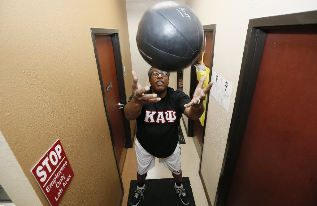 Dallas City councilman Dwaine Caraway tosses a 8-9 pound medicine ball into the air as part of his exercise regimen in November, 2014.
