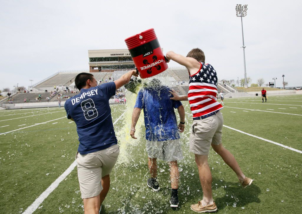 Eric Ramirez gets a Gatorade shower from seniors Joel Carlos (left) and Tyler Zych after a Hebron High win in April 2014.