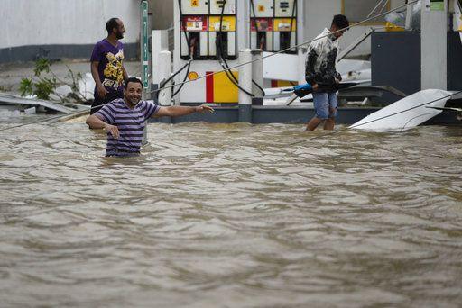 Varias personas caminan cerca de una gasolinera inundada y dañada tras el paso del huracán María, que azotó la región este de la isla, en Humacao, el miércoles 20 de septiembre de 2017. María es el huracán más poderoso que ha castigado a Puerto Rico en más de 80 años. Destruyó cientos de hogares, dejó sin electricidad la isla y convirtió algunas calles en ríos en una embestida que podría agravar la crisis financiera del territorio. Foto AP