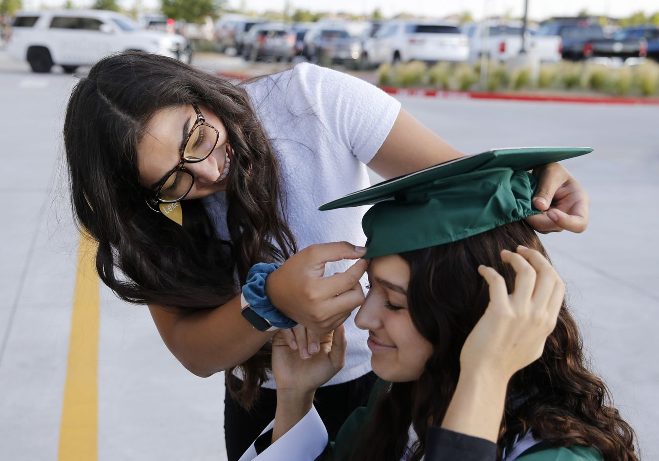 Prosper High School softball player Lexie Bell gets help from her sister Tori Bell with her cap prior to Prosper High School's graduation ceremony at Children's Health Stadium in Prosper, Texas on Friday, June 5, 2020. Bell signed to play softball at St. Edward's University. But she was recently diagnosed with Ewing Sarcoma, a rare form of cancer.
