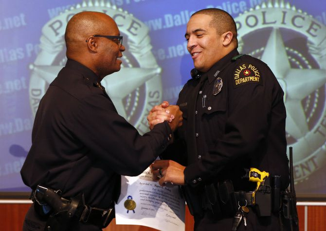 Dallas Police Chief David Brown (left) congratulated Officer Ryan Mabry, one of three officers involved  in the rescue of a man whose SUV plunged into Bachman Lake.