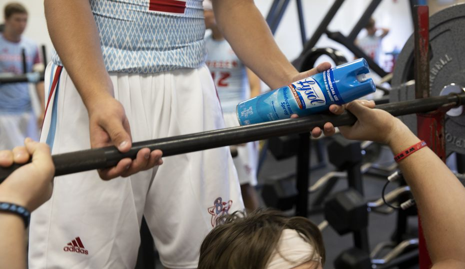 Borden County High School senior Tommy Kingston holds a Lysol bottle while spotting during a work out before practice on Aug. 18, 2020 in Gail.