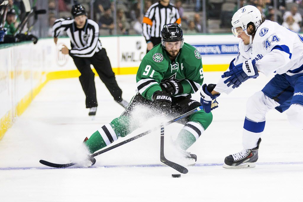 Dallas Stars center Tyler Seguin (91) pushes the puck past Tampa Bay Lightning left wing Tye McGinn (44) during the first period of an NHL preseason hockey game at the American Airlines Center on Saturday, Sept. 26, 2015, in Dallas. (Smiley N. Pool/The Dallas Morning News)