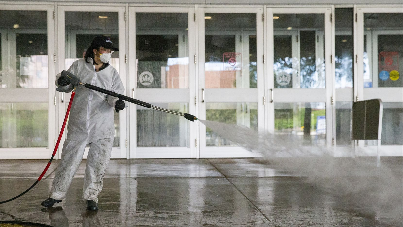 A worker power washes the entrance to Area C at the Kay Bailey Hutchison Convention Center in downtown Dallas on March 29, 2020. Texas Gov. Greg Abbott announced on March 29, 2020, that the US Army Corps of  Engineers and the state are putting up a 250-bed field hospital at the center downtown.  (Juan Figueroa/ The Dallas Morning News)