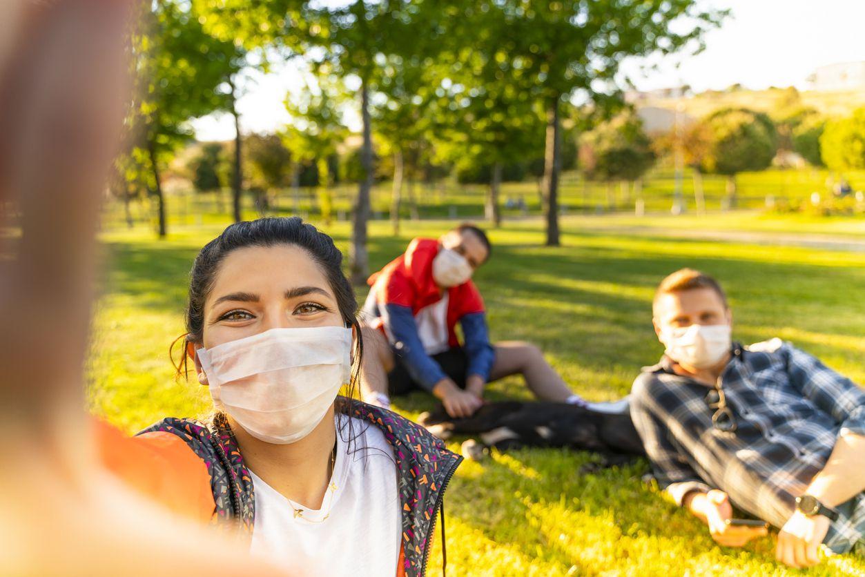 Estudiantes de universidad se reúnen en un parque público.