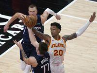 Dallas Mavericks guard Luka Doncic (77) is defended by Atlanta Hawks forward John Collins (20) during the second half of an NBA basketball game Wednesday, Feb. 3, 2021, in Atlanta. Mavericks forward Kristaps Porzingis is at rear.