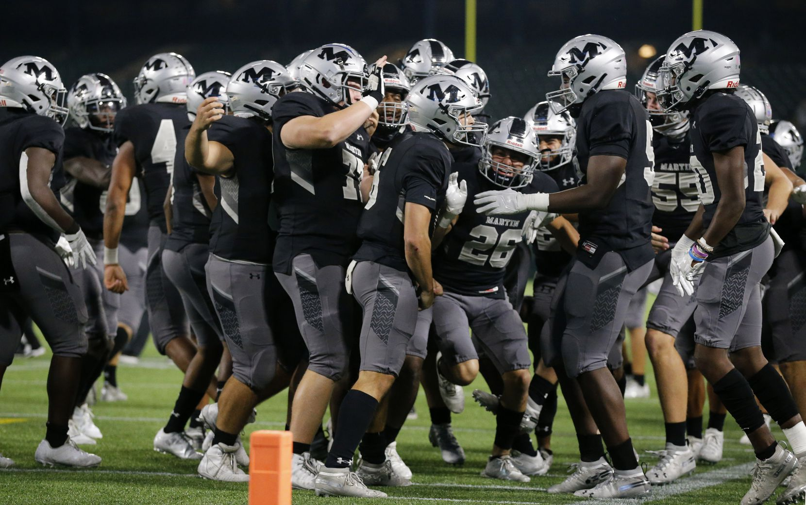 Arlington Martin quarterback Zach Mundell (center) is congratulated by teammates after scoring the winning touchdown in overtime against Arlington Lamar at Globe Life Park in Arlington, Friday, October 30, 2020. Martin defeated Lamar in overtime, 38-31. (Tom Fox/The Dallas Morning News)
