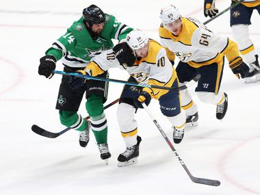 Dallas Stars left wing Jamie Benn (14) and Nashville Predators center Colton Sissons (10) go after the puck during the first period of play in the Stars home opener at American Airlines Center on Friday, January 22, 2021 in Dallas.