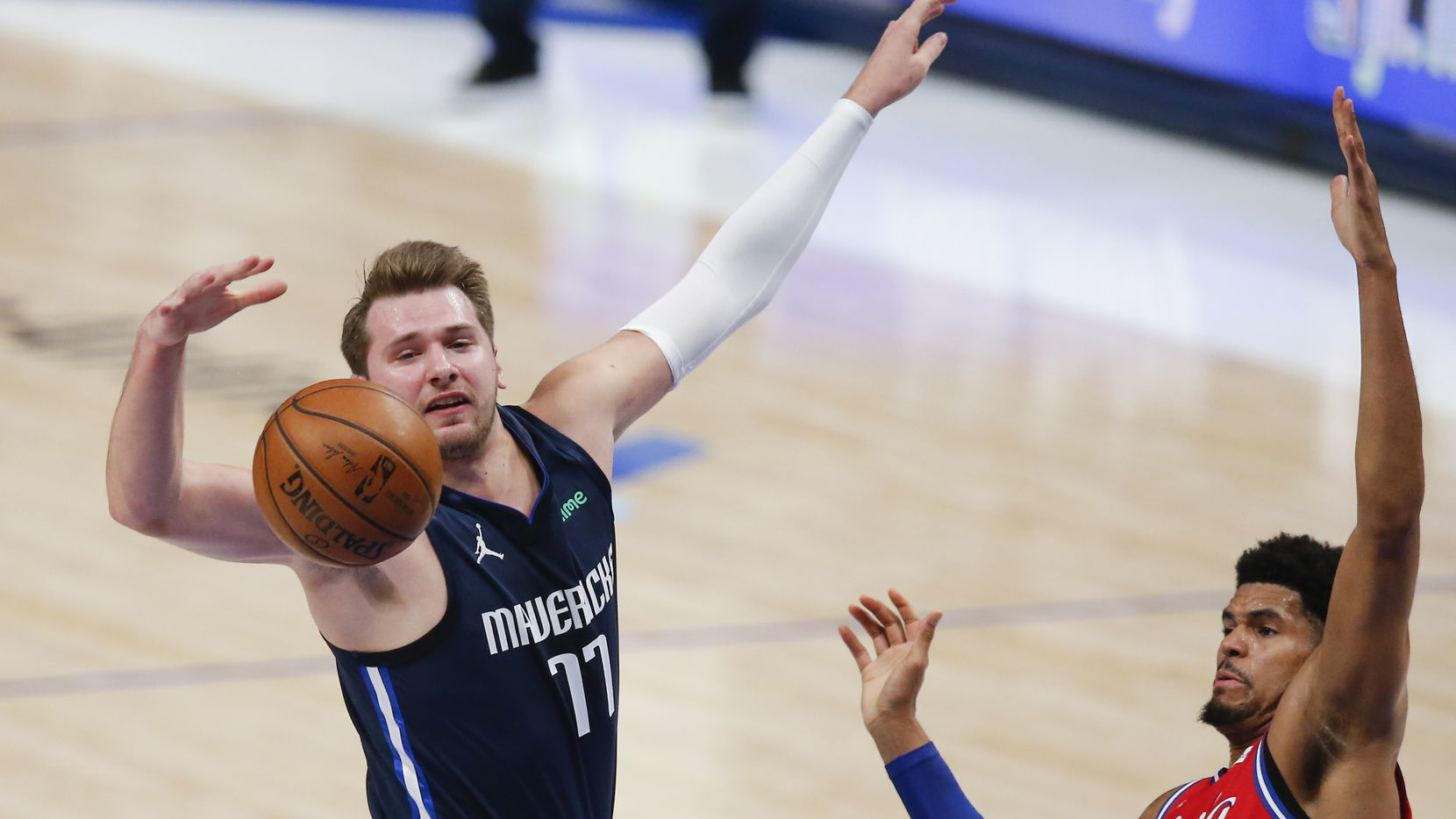 Dallas Mavericks guard Luka Doncic (77) and Philadelphia 76ers forward Tobias Harris (12) battle for a loose ball during the first half of an NBA basketball game in Dallas, Monday, April 12, 2021.