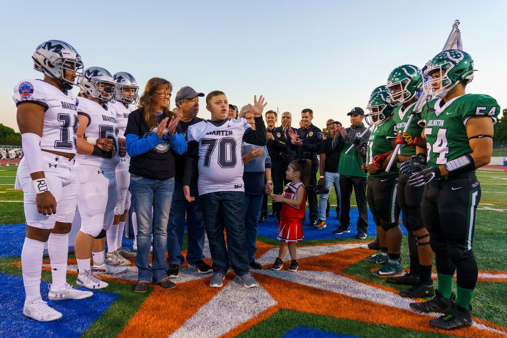 Elisha Castaneda, the son of Grand Prairie police officer A.J. Castaneda, who died in the line of duty in June, waves to the crowd as he serves as the honorary captain for a high school football game between Arlington and Arlington Martin at UTA's Maverick Stadium on Friday, Oct. 18, 2019, in Arlington, Texas. (Smiley N. Pool/The Dallas Morning News)