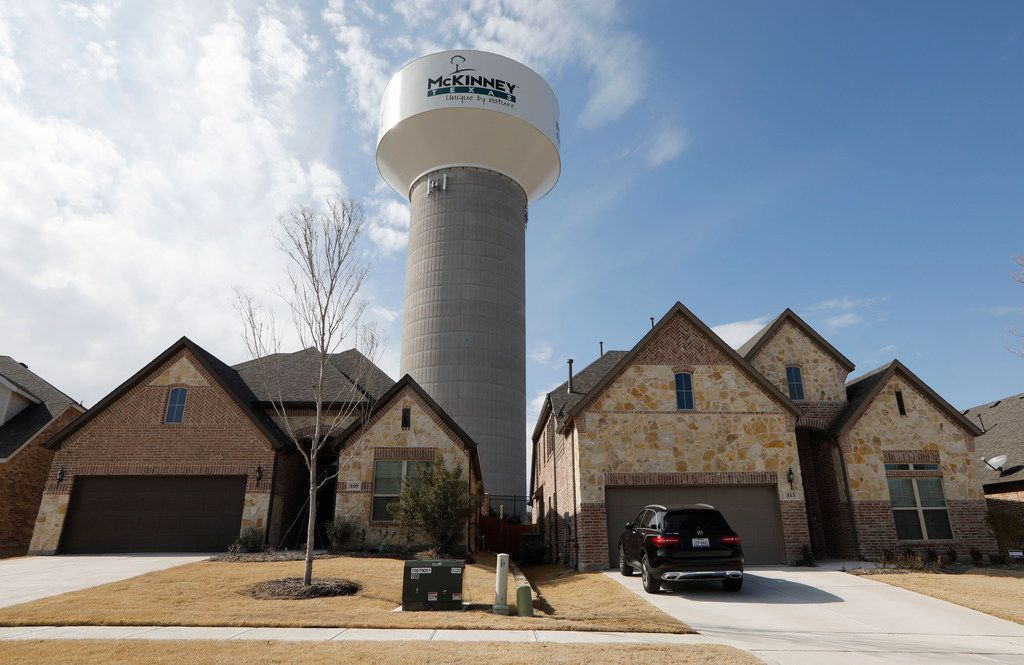 A McKinney water tower looms behind new homes in the 100 block of Leadville Way in McKinney on Wednesday.