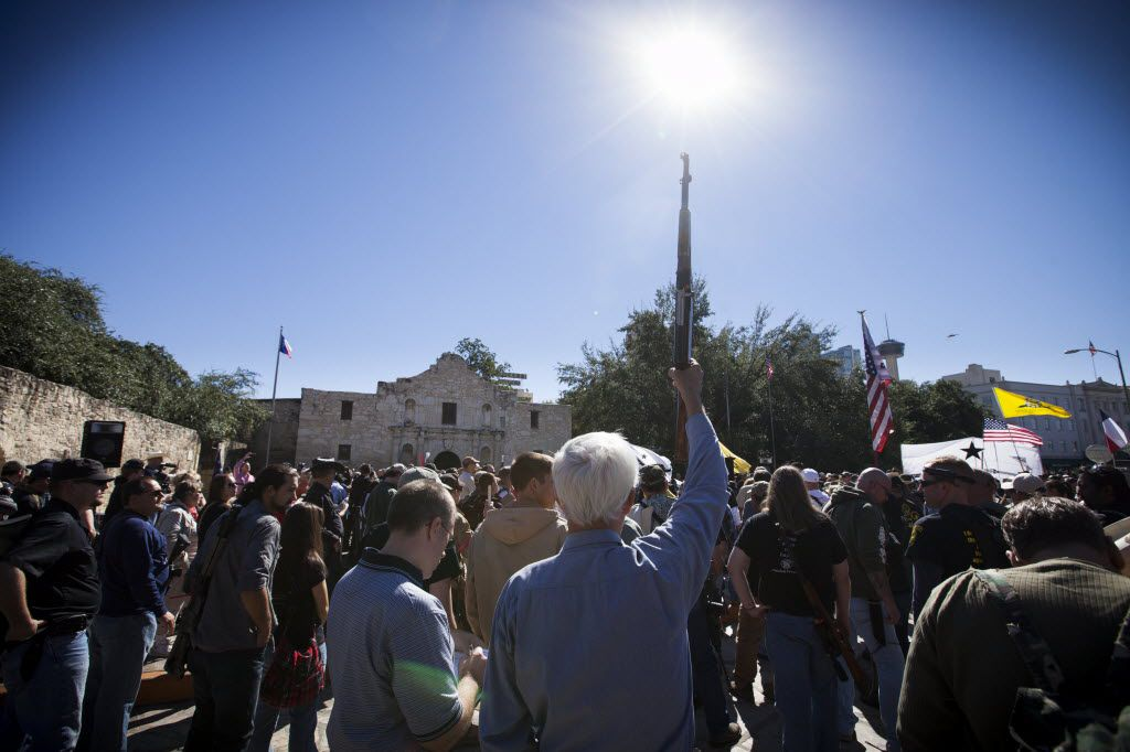 A demonstrator raises his rifle during a pro-gun rally at the Alamo in San Antonio, Oct. 19, 2013. (Michael Stravato/The New York Times)