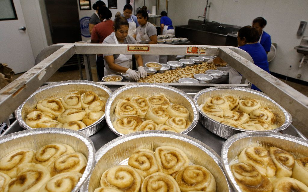 Nancy Rodriguez (center) places cinnamon rolls in a pan at RoRo's Baking Company in Dallas.