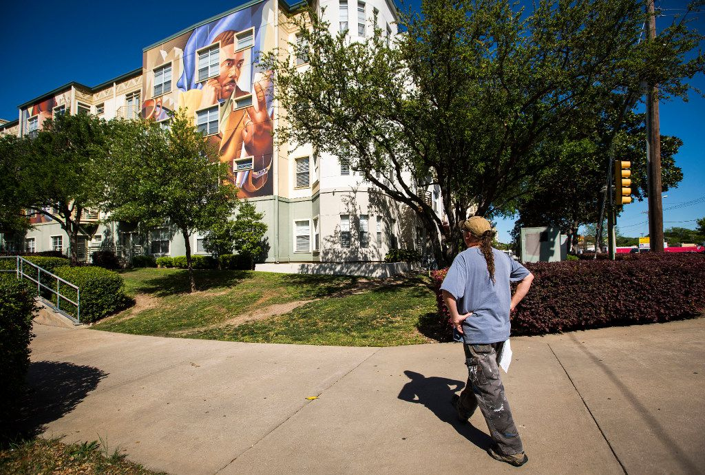 Artist Chris Arnold watches painters erase the murals he and Jeff Garrison painted in 2008. The remaining murals are due to disappear next week. (Smiley N. Pool/The Dallas Morning News)