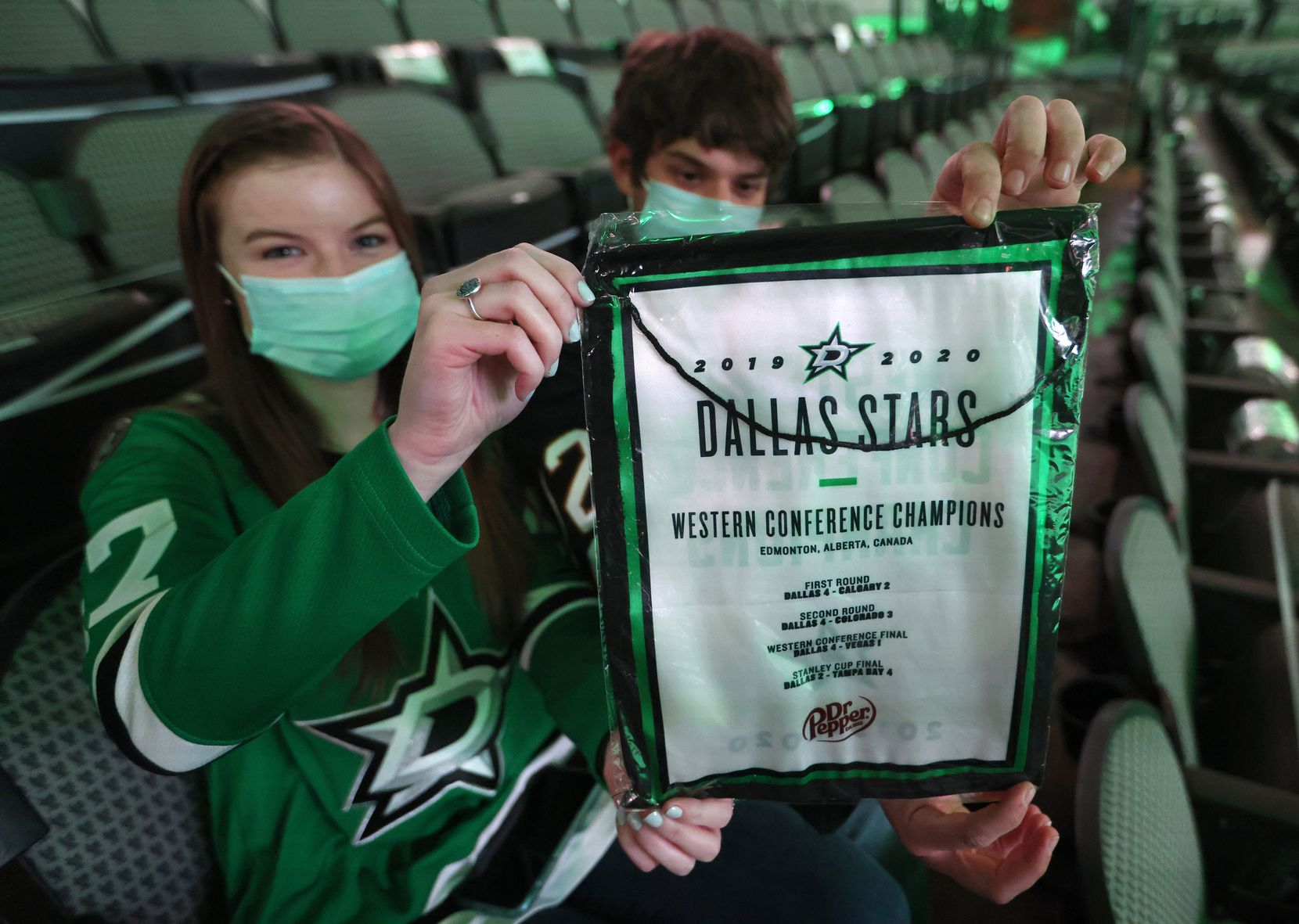 Kendra Maher and Daniel Mignault of Dallas hold up one of the replica banners given to fans prior to the start of a game between the Dallas Stars and Nashville Predators in the Stars home opener at American Airlines Center on Friday, January 22, 2021in Dallas. (Vernon Bryant/The Dallas Morning News)