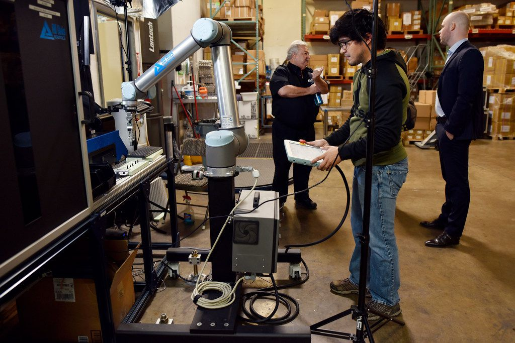 An All Axis Machining employee programs a robot with an OnRobot electric gripper to conduct a task in the Dallas machine shop.