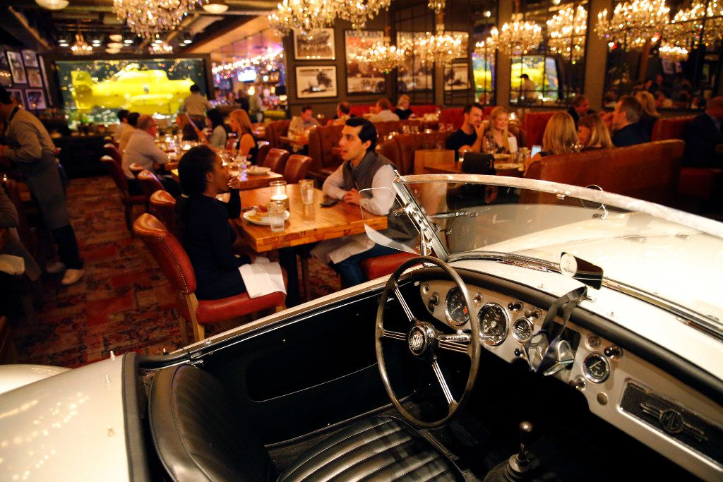 A 1961 MG is an unexpected dinner guest at Town Hearth, chef Nick Badovinus' new restaurant in the Dallas Design District.  Sixty-four crystal chandeliers illuminate the dining room, which also features an aquarium holding a World War II era minesweeper.