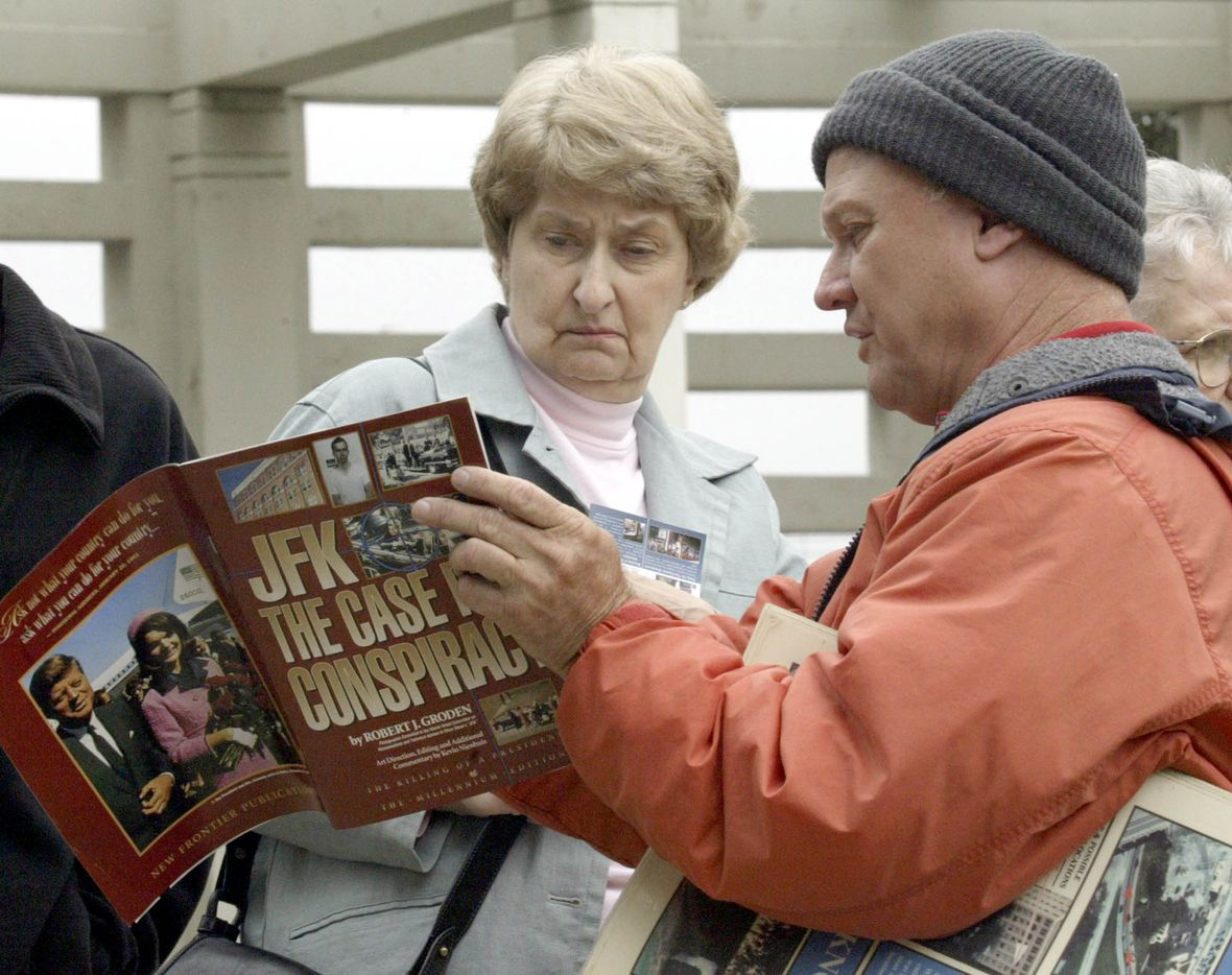 Vendor Fred Browning, right, shows tourist Nancy Sumrall, from Cedar Park, Texas, a publication on theories about President John F. Kennedy's assassination in Dallas' Dealey Plaza in 2003.