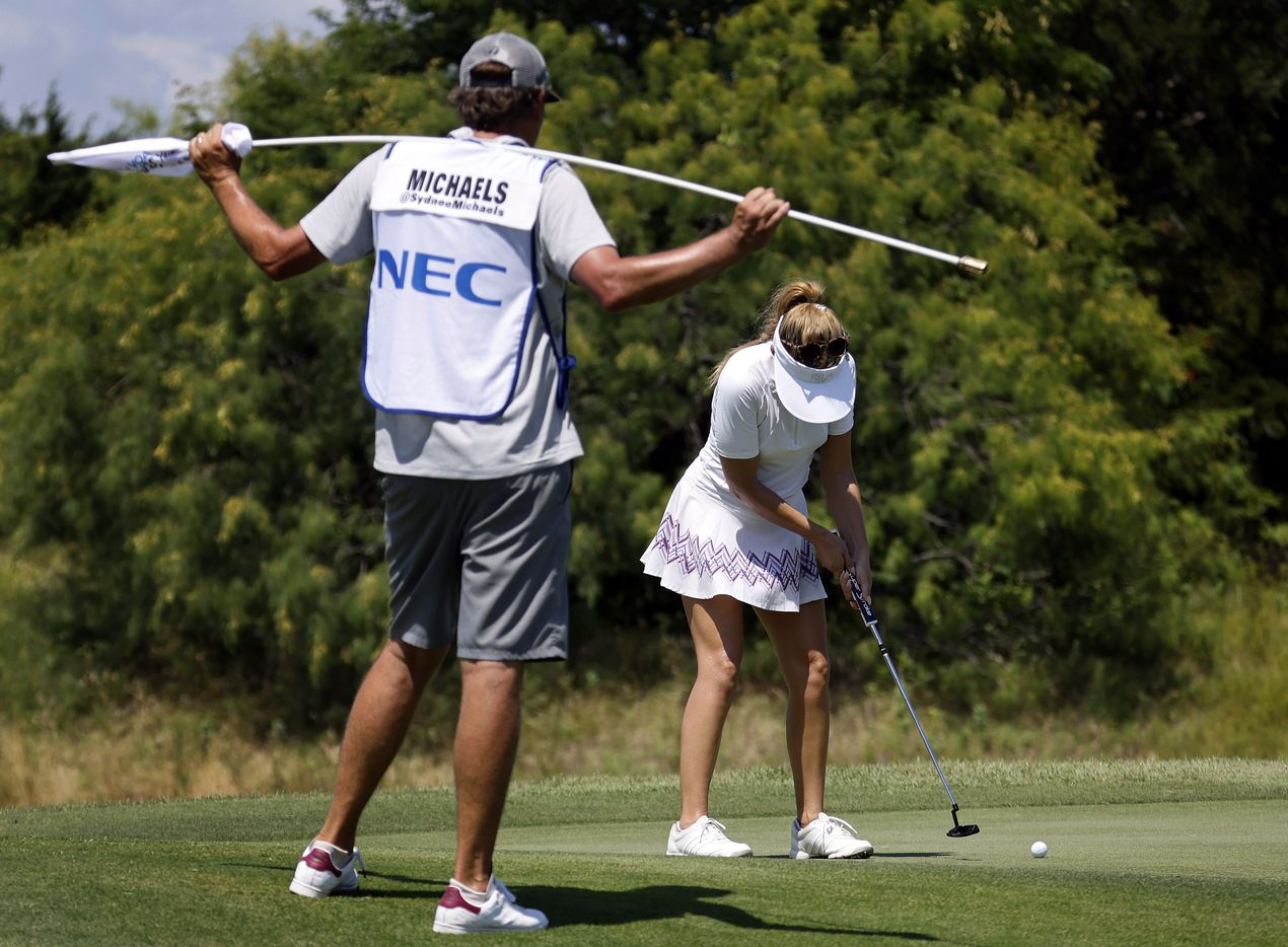 With her caddie looking on, professional golfer Sydnee Michaels putts on No. 17 during the opening round of the LPGA VOA Classic at the Old American Golf Club in The Colony, Texas, Thursday, July 1, 2021. (Tom Fox/The Dallas Morning News)