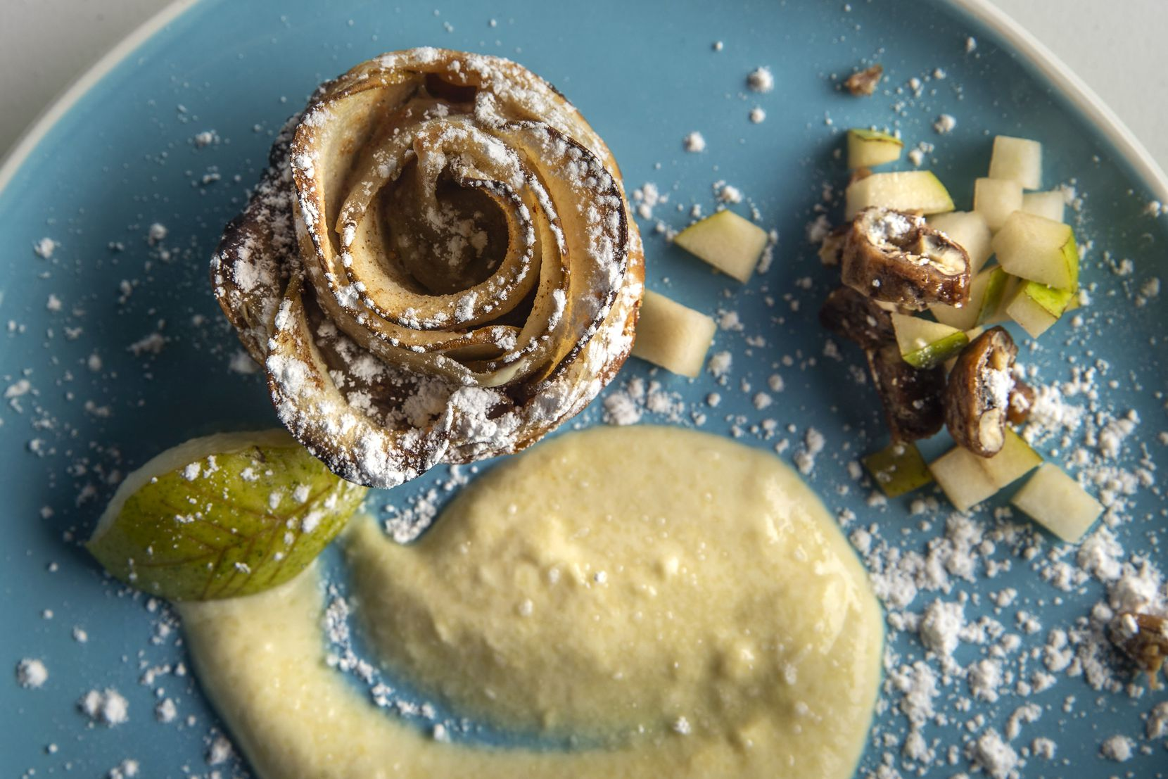 A pear rose tart plated on pear creme anglaise