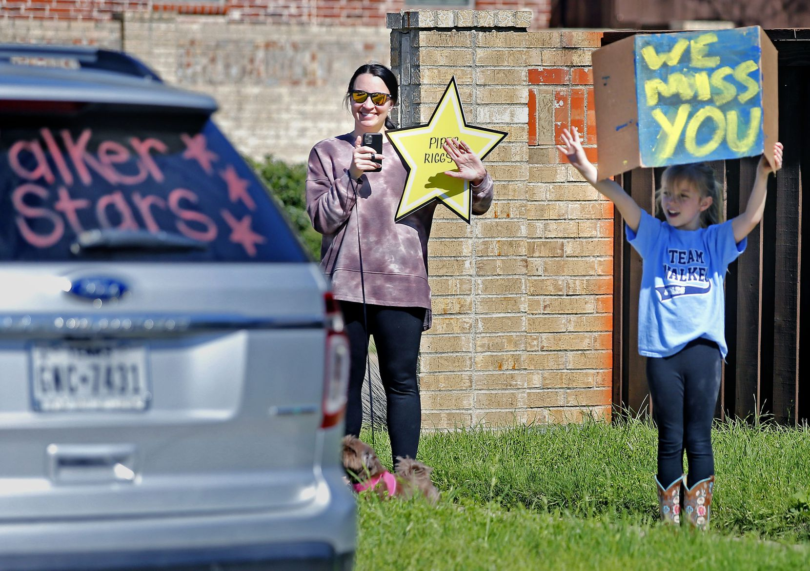 Piper Riggs (right), 8, and her mother Jessica wave as teachers from Walker Elementary School in the McKinney School District paraded in their vehicles past students homes in the school's neighborhood in McKinney on Tuesday, March 24, 2020. The teachers held the event to do something fun to connect with their students while school is being held remotely inside homes during the time of coronavirus.