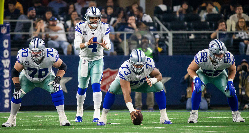 Dallas Cowboys quarterback Dak Prescott (4) lines up behind offensive guard Zack Martin (70), center Joe Looney (73) and offensive guard Connor Williams (52) during the second half of an NFL wild-card playoff football game against the Seattle Seahawks at AT&T Stadium on Saturday, Jan. 5, 2019, in Arlington. The Cowboys won the game 24-22. (Smiley N. Pool/The Dallas Morning News)