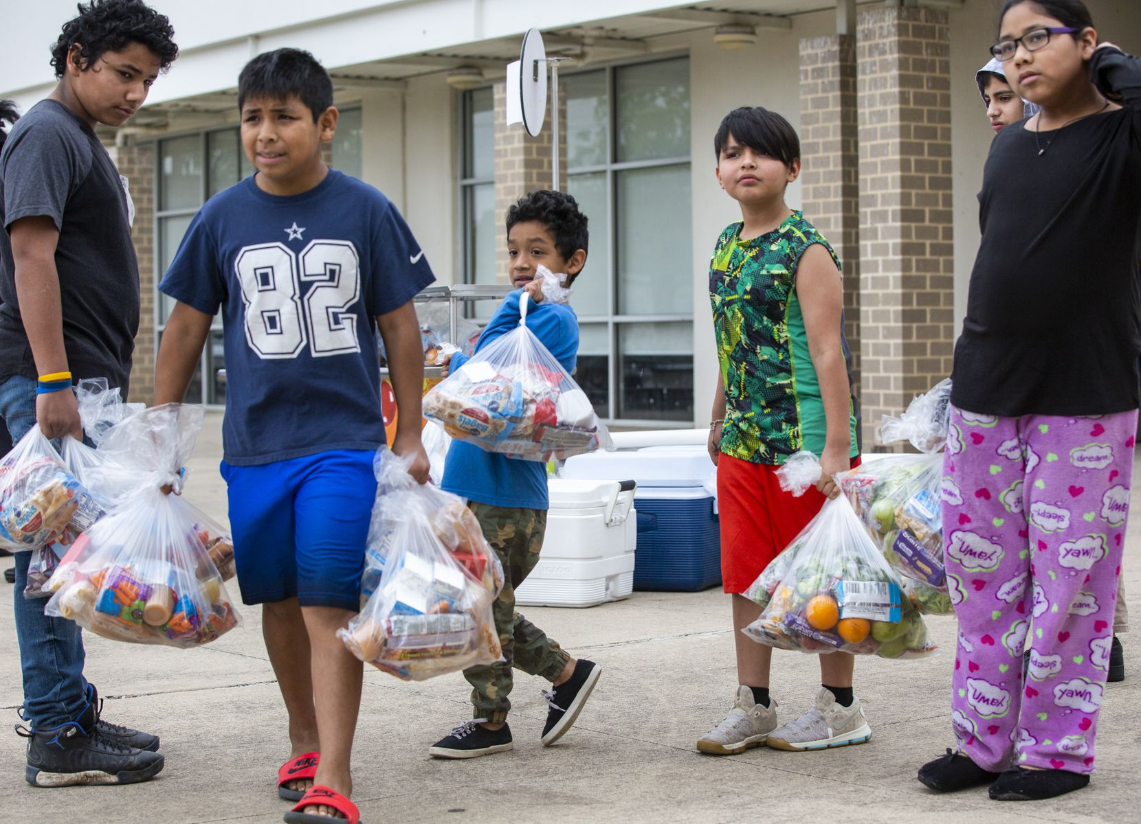 Siblings (from left) Anthony Sanchez, 13, Isaiah Sanchez, 12, Joseph Avaral, 7, Adrian Saldana, 9, and Crystal Sanchez, 14, received  meals at Medrano on Thursday.
