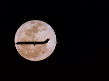 A full moon illuminates a plane's landing at DFW Airport.