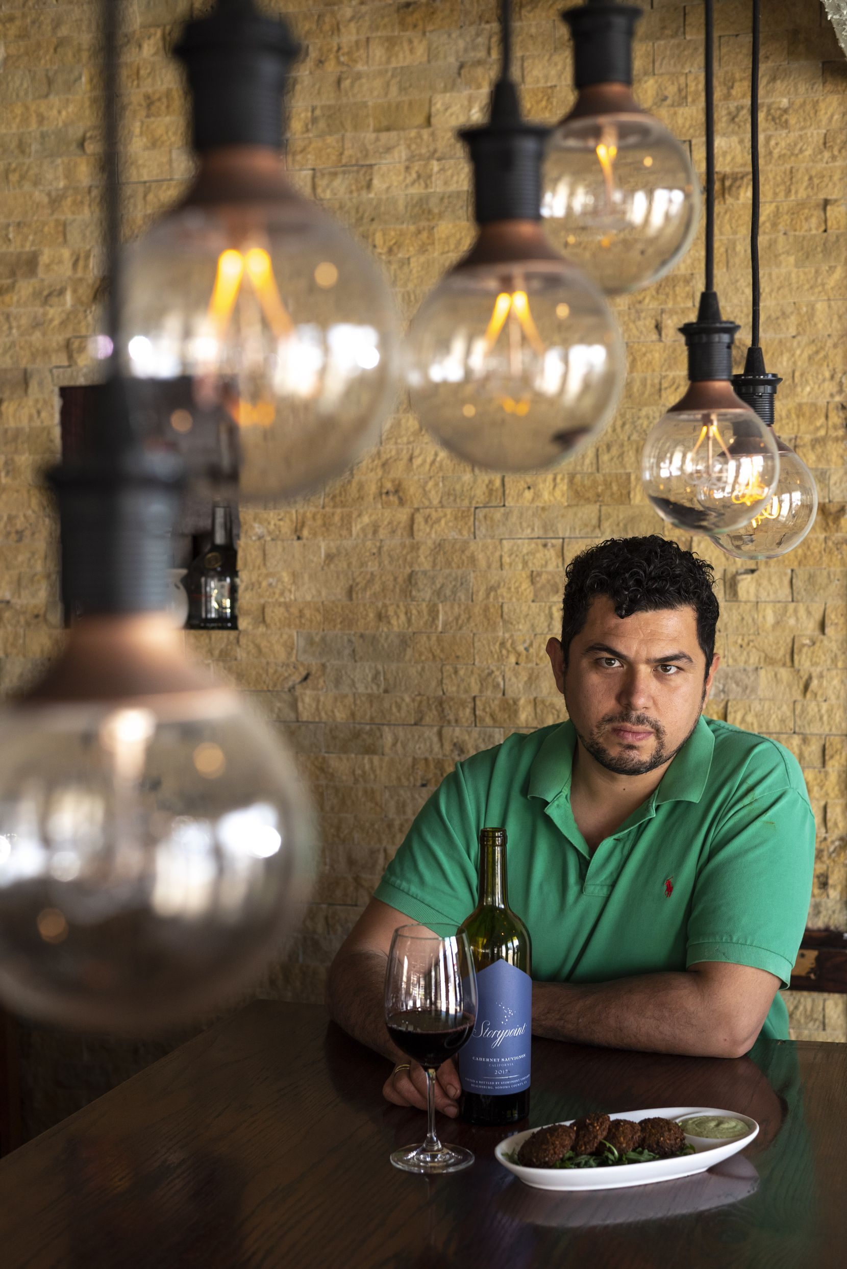 Chef and owner Sirzat Demir of Selda Mediterranean Grill in Dallas, and a dish of falafel, fried chickpea patties, served with a glass of wine.