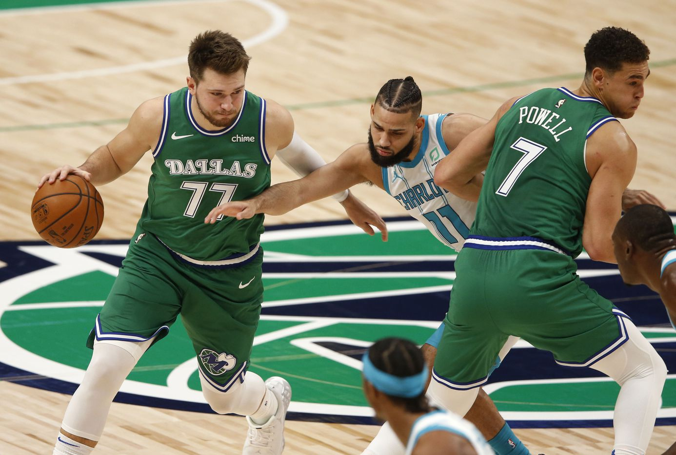 Dallas Mavericks guard Luka Doncic (77) uses a screen from Dallas Mavericks center Dwight Powell (7) to get by Charlotte Hornets forward Cody Martin (11) during the first quarter of play in the home opener at American Airlines Center on Wednesday, December 30, 2020 in Dallas. (Vernon Bryant/The Dallas Morning News)