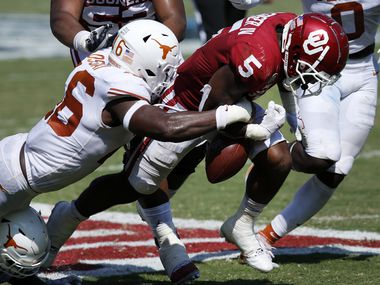 Texas Longhorns linebacker Joseph Ossai (46) forces a fumble by Oklahoma Sooners running back T.J. Pledger (5) during the second quarter of the Red River Rivalry at the Cotton Bowl in Dallas, Saturday, October 10, 2020. Longhorns recovered, Oklahoma won in quadruple overtime, 53-45. (Tom Fox/The Dallas Morning News)