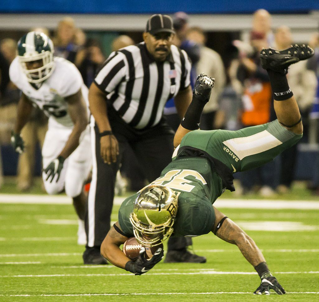 Baylor running back Shock Linwood (32) tumbles to the ground after being tripped up during the second half of the Goodyear Cotton Bowl Classic at AT&T Stadium on Thursday, Jan. 1, 2015, in Arlington.  ( Smiley N. Pool / The Dallas Morning News )