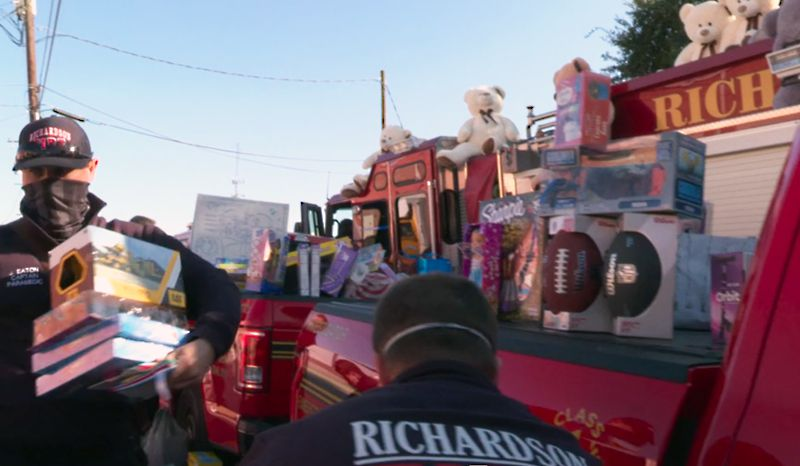 Richardson firefighters are shown in this video screenshot delivering toys and canned food to the nonprofit Network of Community Ministries for its annual holiday event for disadvantaged families.