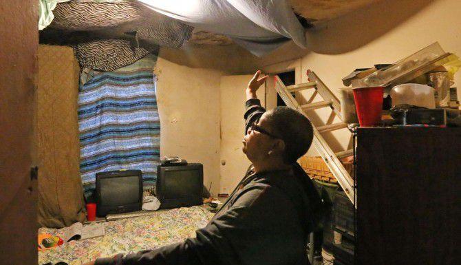 Joanne Bonner muestra el techo dañado en la casa donde vive con su familia, en Lawrence Street, en el sur de Dallas.(LOIS DeLUCA)