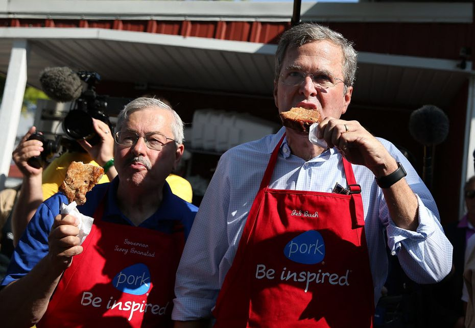 Former Florida Gov. Jeb Bush and then-Iowa Gov. Terry Branstad eat pork chop on a stick at the 2015 Iowa State Fair. Branstad is now ambassador to China.
