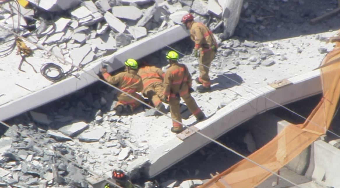 In this screen image from WPLG-TV in Miami, rescuers look through the rubble after a bridge collapsed Thursday at Florida International University.