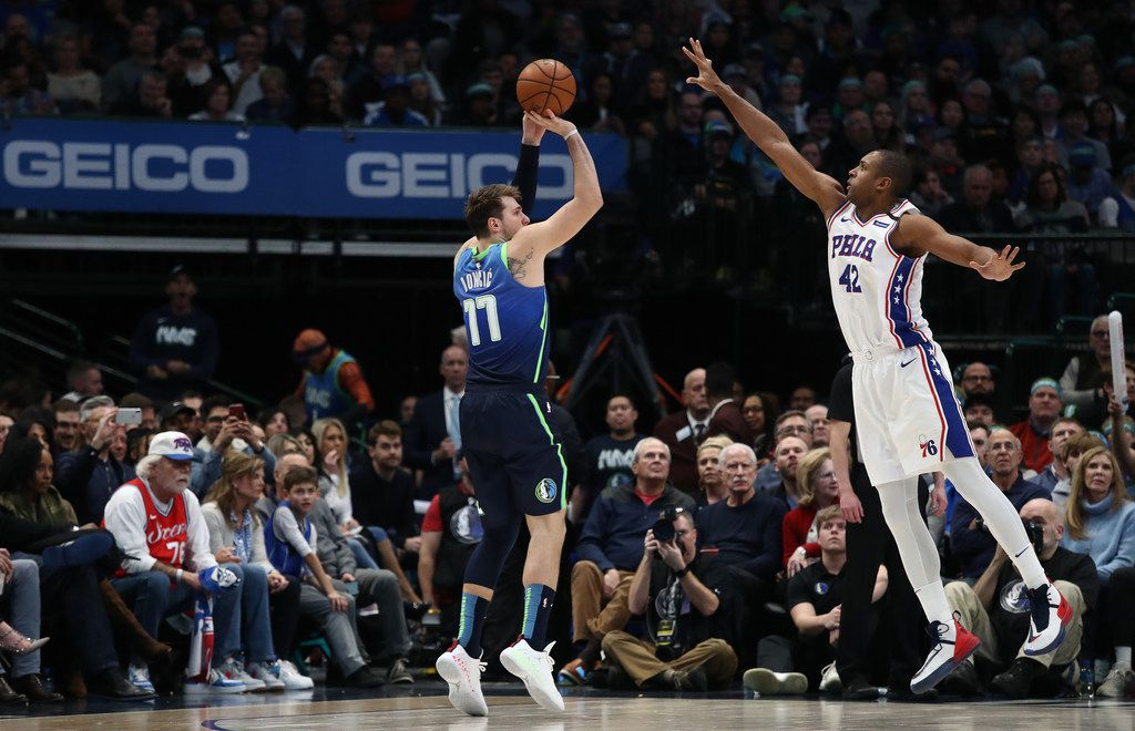 DALLAS, TEXAS - JANUARY 11:   Luka Doncic #77 of the Dallas Mavericks takes a shot against Al Horford #42 of the Philadelphia 76ers at American Airlines Center on January 11, 2020 in Dallas, Texas.  NOTE TO USER: User expressly acknowledges and agrees that, by downloading and or using this photograph, User is consenting to the terms and conditions of the Getty Images License Agreement.  (Photo by Ronald Martinez/Getty Images)