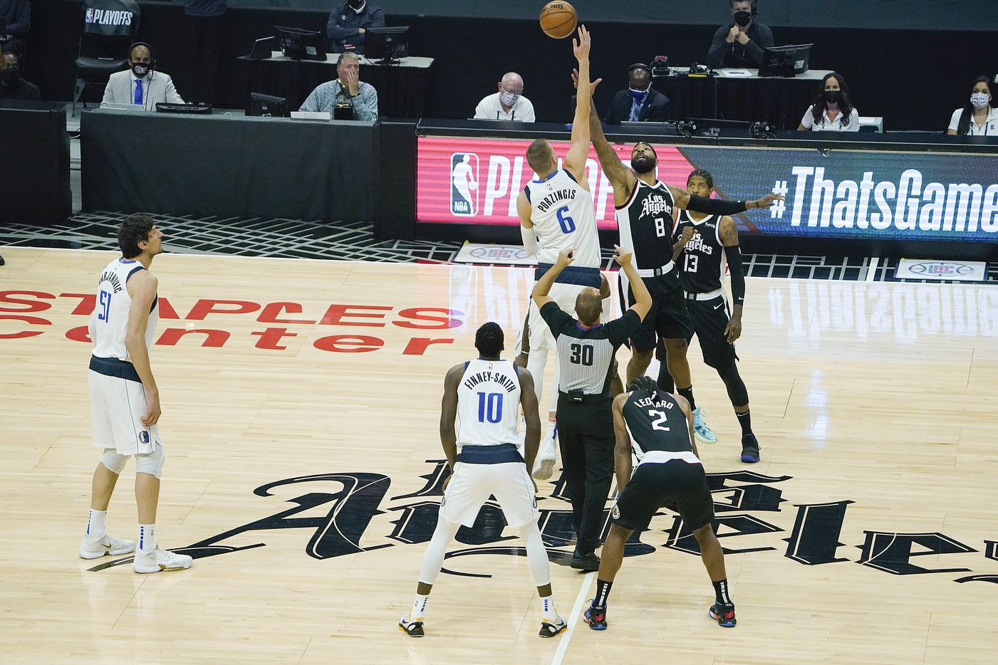 Dallas Mavericks center Kristaps Porzingis (6) wins the opening tipoff of an NBA playoff basketball game over LA Clippers forward Marcus Morris Sr. (8) at the Staples Center on Wednesday, June 2, 2021, in Los Angeles.  (Smiley N. Pool/The Dallas Morning News)