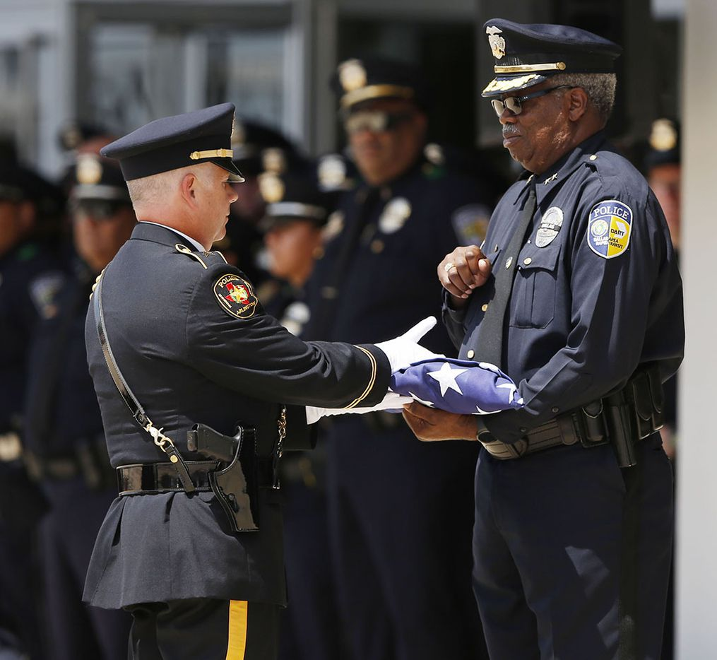 Arlington Honor Guard hands the flag over to a DART official to hand to the family during a memorial service for DART Officer Brent Thompson at The Potter's House in Dallas on Wednesday, July 13, 2016. Thompson was one of five officers killed last week when a gunman opened fire during a Black Lives Matter rally in downtown Dallas.