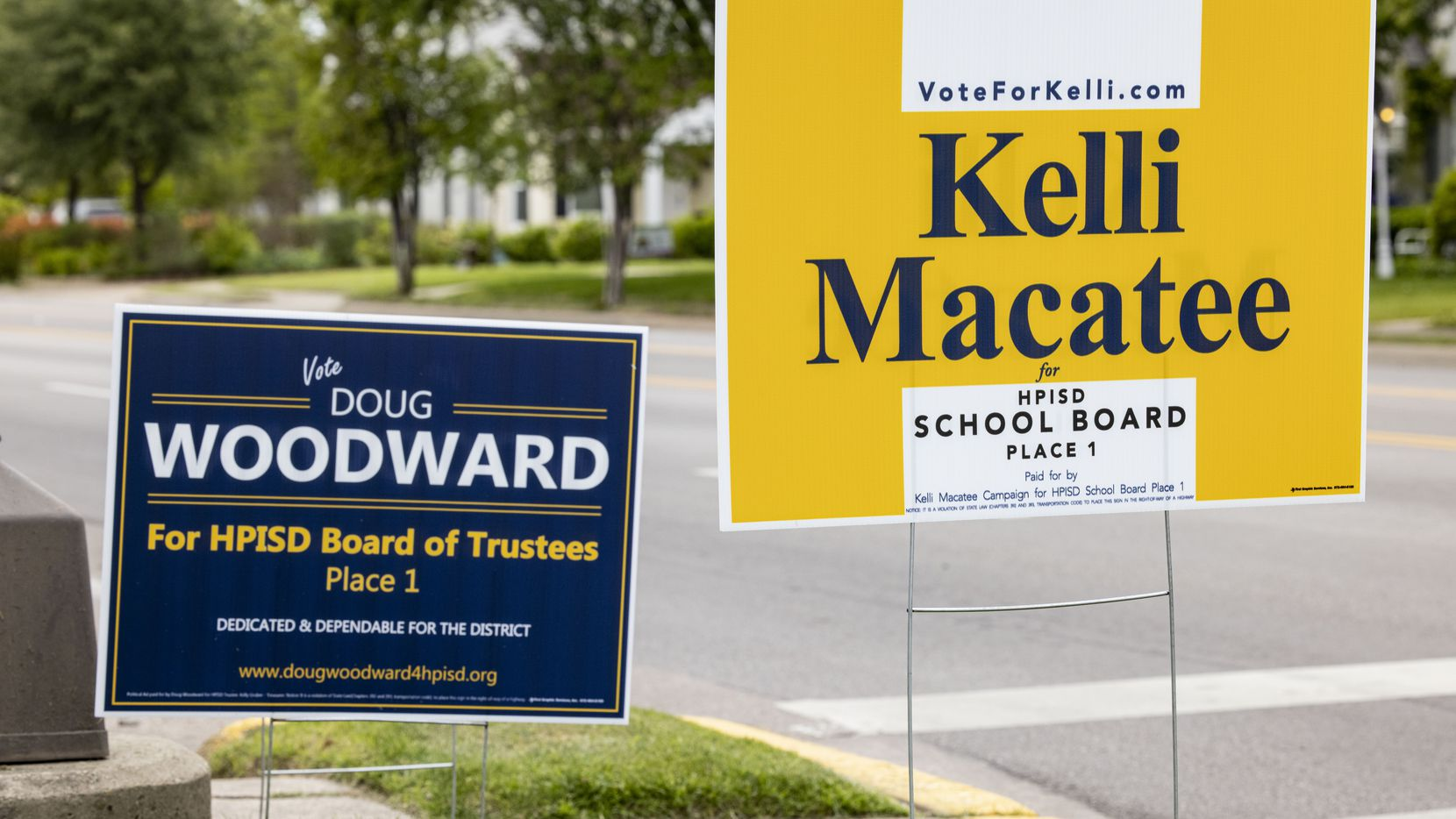 Kellie Macatee and Doug Woodward campaign signs photographed outside of the Highland Park ISD administration building on April 21, 2021, in Dallas.
