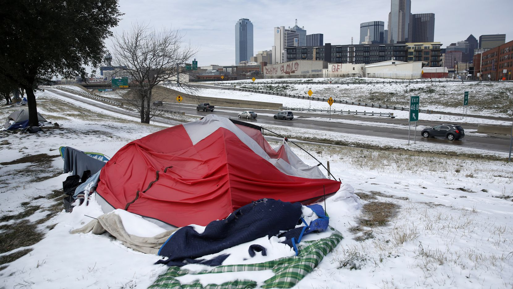 Snow-covered tents pitched along Interstate 30 were abandoned by their owners as a snow storm and subfreezing temperatures rolled into downtown Dallas. A nearby warming shelter at the Kay Bailey Hutchison Convention Center was set up by OurCalling and was housing about 700 people who found refuge from the deadly cold temperatures in Hall E-F.