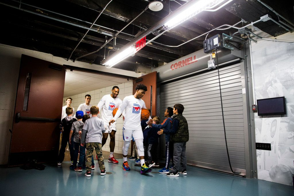 Southern Methodist Mustangs players are greeted by children as they walk from the locker room to the court before a basketball game between SMU and University of Houston on Saturday, February 15, 2020 at Moody Coliseum in Dallas. (Ashley Landis/The Dallas Morning News)