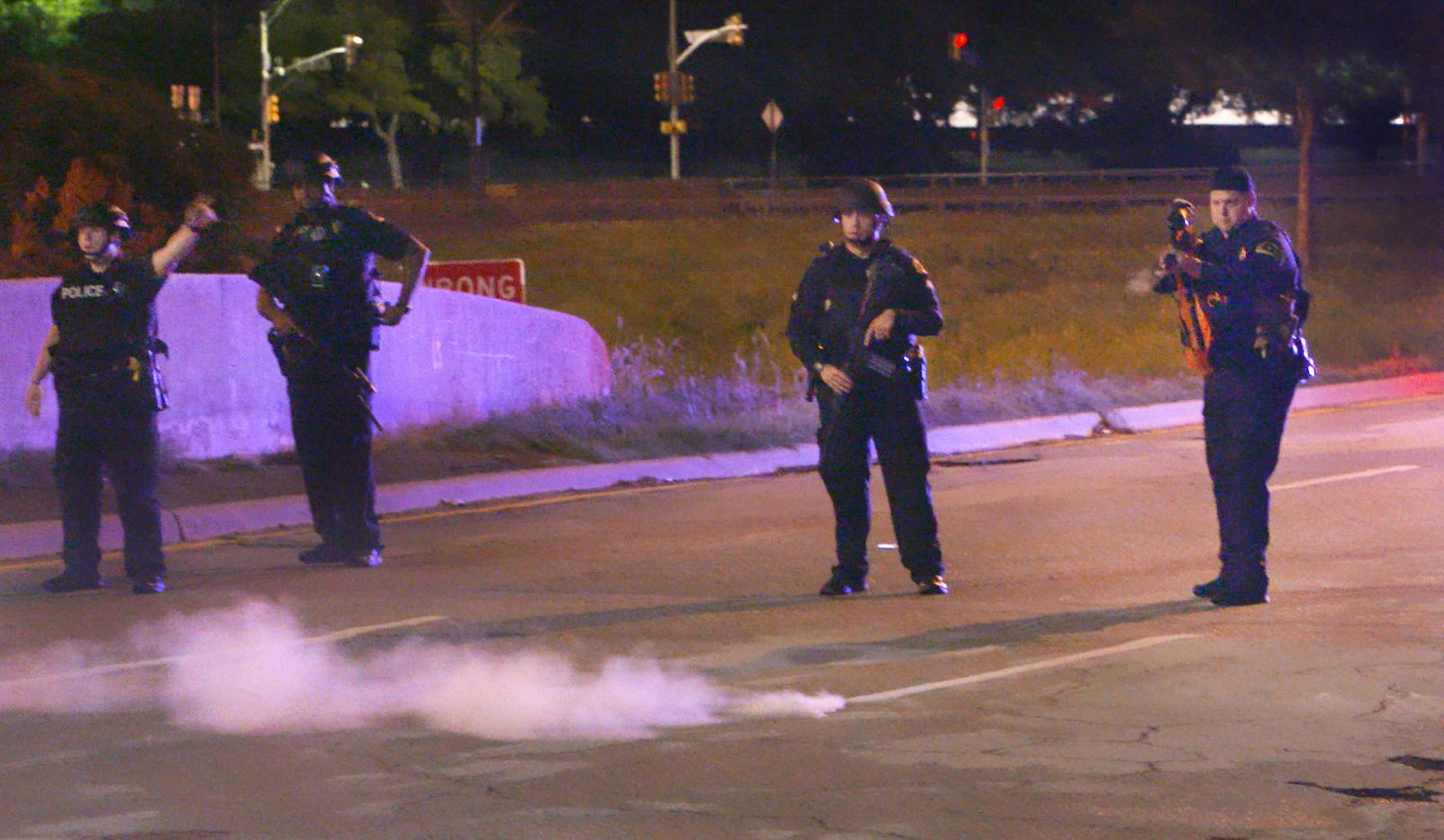A Dallas police officer fires pepper balls at a crowd during Monday night's protest against police brutality. The protest blocked traffic on Cadiz Street in Dallas. Community activists organized the rally to protest Officer Amber Guyger's killing of 26-year-old Botham Jean on Thursday night.
