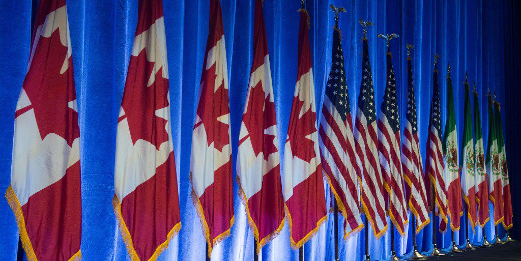 The flags of Canada, the United States, and Mexico lined the stage before the start of the negotiations for the modernization of NAFTA in mid-August in Washington. (Paul J. Richards/Agence France-Presse)