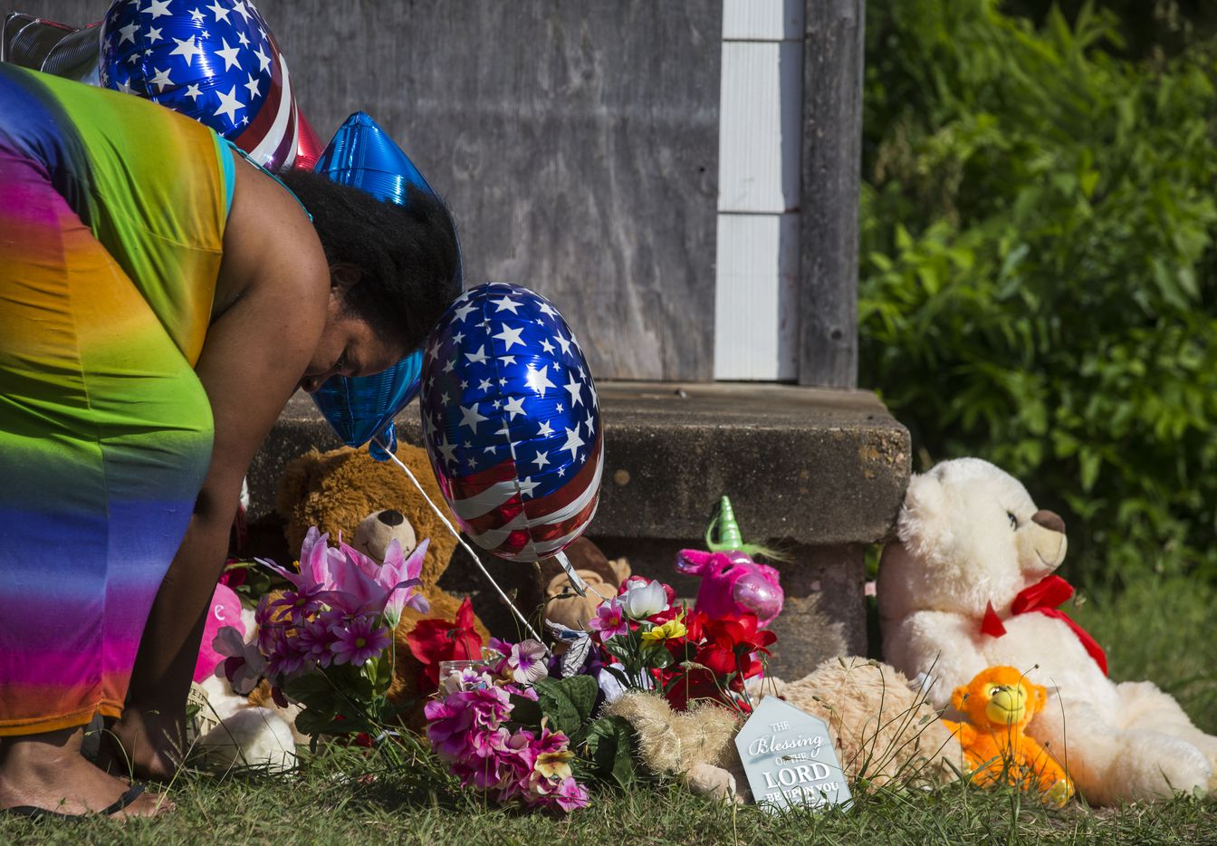 Adrian Moseley, of Dallas, plants a flower at a memorial as balloons and flowers wave in the wind at a home in the 2200 block of East Kiest Boulevard where a missing Lancaster teenager and a man were found dead overnight Sunday, July 2, 2017, in Dallas.