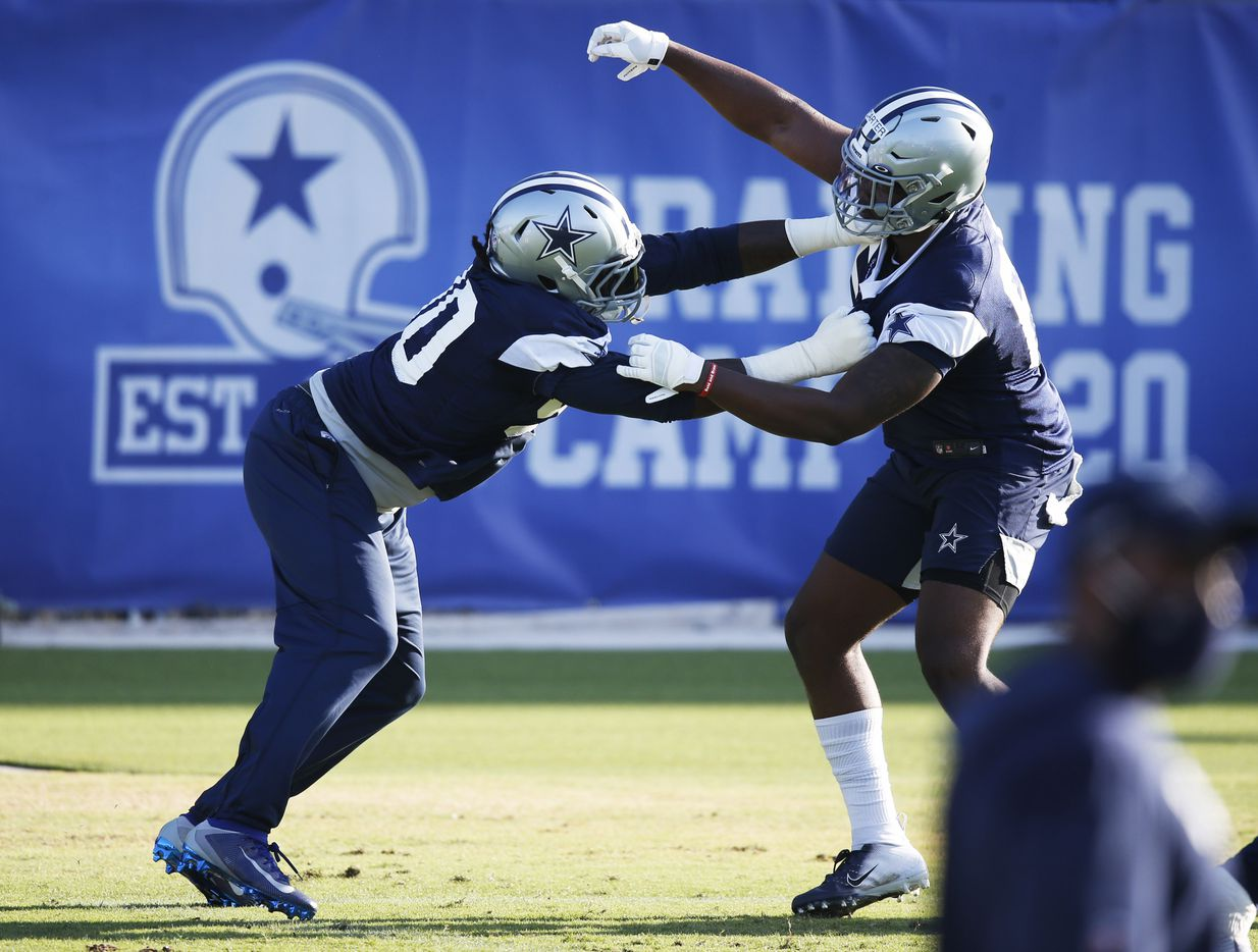 Dallas Cowboys defensive end DeMarcus Lawrence (90) and Dallas Cowboys defensive end Ron'Dell Carter (68) work through a drill during the first day of training camp at Dallas Cowboys headquarters at The Star in Frisco, Texas on Friday, August 14, 2020. (Vernon Bryant/The Dallas Morning News)