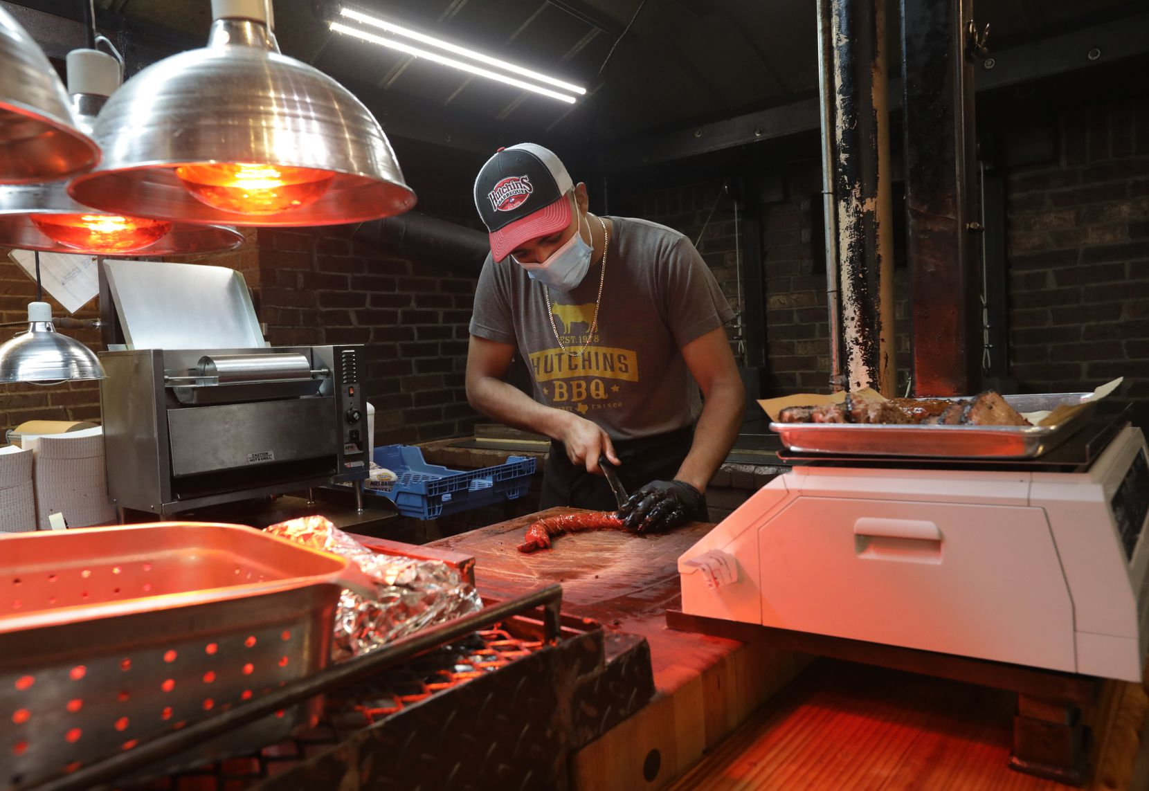 Jonny Magno cuts some meat at Hutchins BBQ in McKinney.