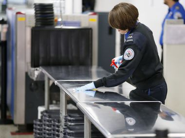 A TSA agent wipes down a table at a security checkpoint in Terminal C at DFW International Airport on April 8, 2020. The coronavirus pandemic has had a widespread impact on the travel industry.