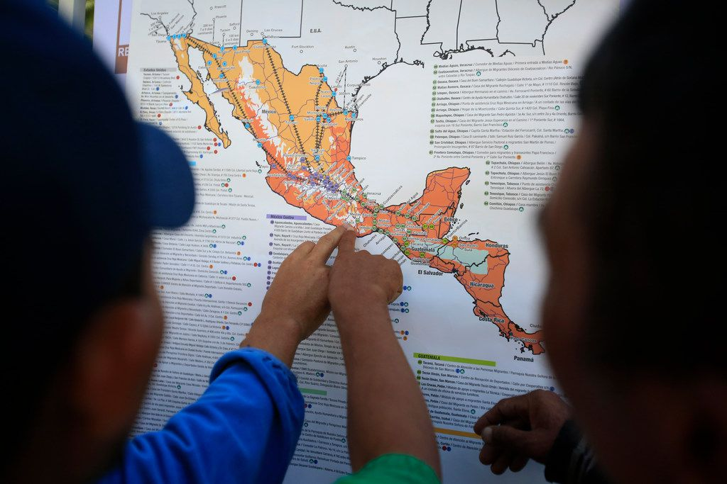 Migrants discuss their journey using a map posted inside the sports complex where thousands of migrants have been camped out for several days in Mexico City on Friday, Nov. 9, 2018.